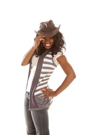 cowgirl hat: una mujer de camisa a rayas aferrarse a el ala de su sombrero de vaquera.