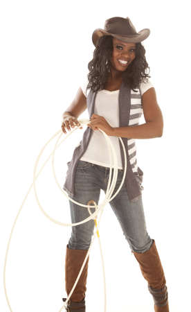 An African American in her cowgirl hat and holding on to a rope with a smile on her face. photo