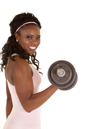 weight lifting: a woman with a big smile on her face lifting a weight.