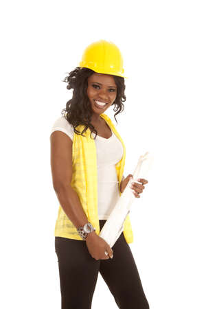 project: a woman in her construction clothes with hard hat and her blue prints with a smile on her face.