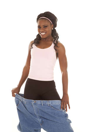 A woman showing off her healthy life by holding out her big pants. photo