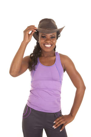 A woman in her workout clothes smiling with her cowgirl hat on .