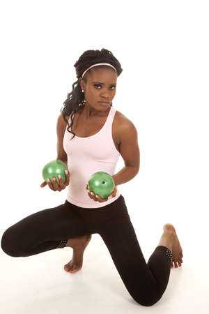 weighted: a woman with green weighted balls working out with a serious expression on her face. Stock Photo