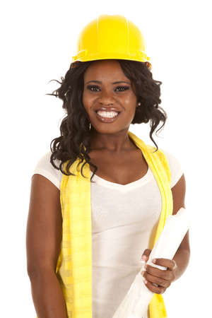 a woman in her construction hard hat holding on to her blueprints with a smile on her face.