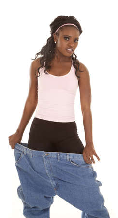 A woman with a small smile on her lips holding on to her big pants. Stock Photo - 15849177