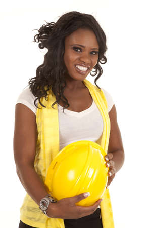 A woman with a big smile on her face holding on to her yellow hard hat. photo