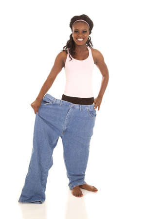a woman standing in one leg of her pants with a smile on her face. photo