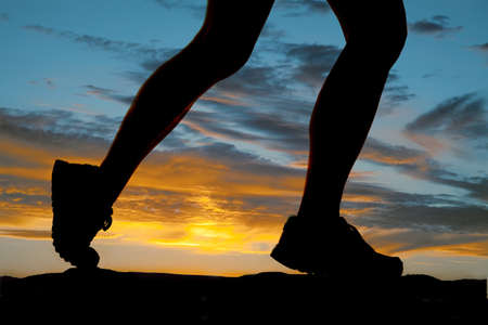 walk: A woman running in the sunset legs silhouette. Stock Photo