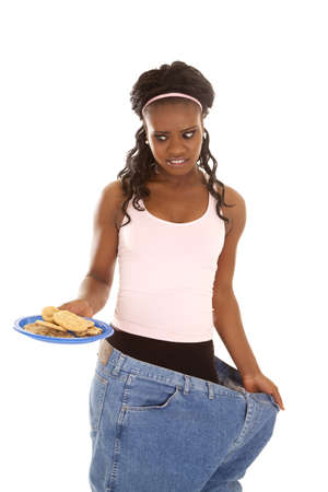 a woman in her big pants looking down at a plate of cookies with a funny expression. photo