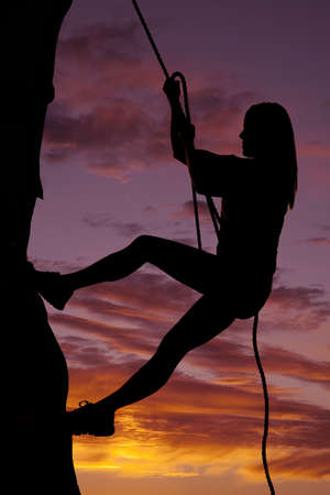 A woman is climbing a rock wall in the sunset. photo