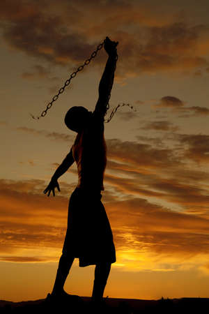 A silhouette of a man in the outdoors swinging a chain in the sky Stock Photo - 15849507