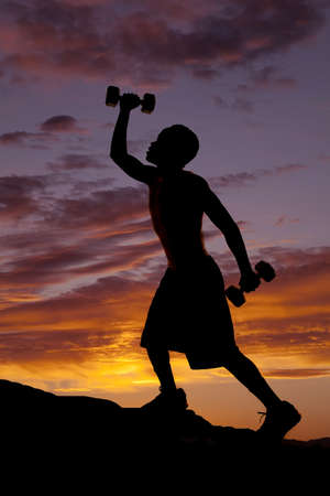 A silhouette of a man climbing up a hill working out with weights. Stock Photo - 15849501