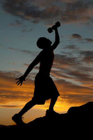 A silhouette of a man going up a hill working out and exercising with weights. Stock Photo - 15849502