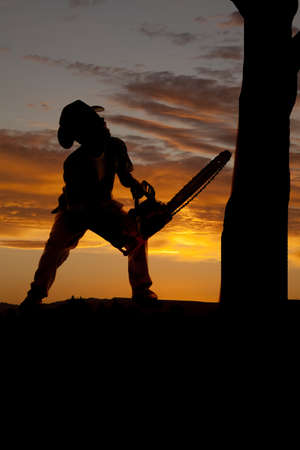 A silhouette of a cowboy with his chainsaw getting ready to cut down a tree. photo