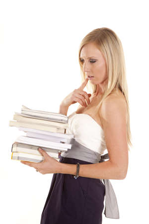 a woman in her dress thinking about the stack of books she has in her hands. Stock Photo - 15849500