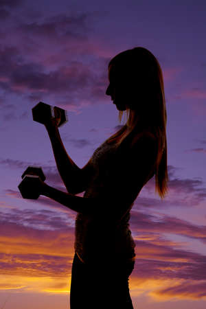a silhouette of a woman working out with weights with a colorful sky in the background. photo