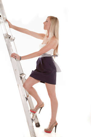 a woman climbing up the ladder in her heels and dress photo