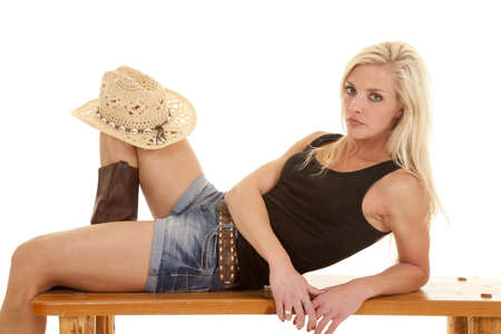 A woman is laying with a cowboy hat on her knee. photo