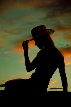 vaqueritas: Una vaquera est� sentado en la puesta de sol sosteniendo su sombrero. Foto de archivo