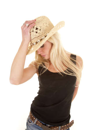 A woman is holding a cowboy hat and looking down.  photo