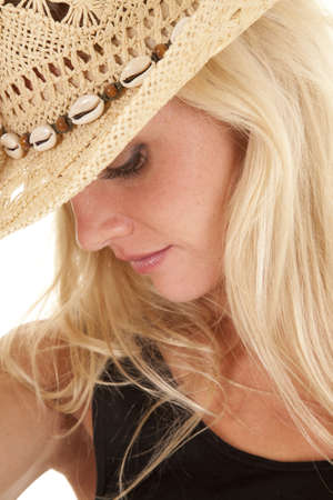 A woman in a cowgirl hat is looking down.  A close up of her face.  스톡 콘텐츠