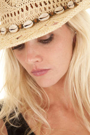 A portrait of a woman in a cowgirl hat.  She is looking down with a serious expression on her face. photo