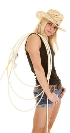 sexy cowgirl: A cowgirl is standing with a rope on her shoulder looking.