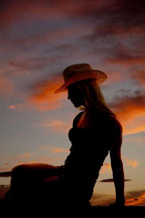 vaqueras: Una vaquera est� sentado en la puesta del sol como una silueta.