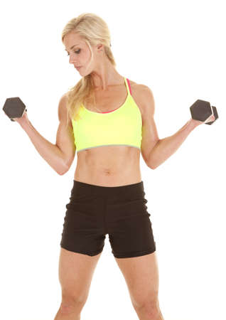 strong: A woman in a green sports bra is curling some dumbbells. Stock Photo