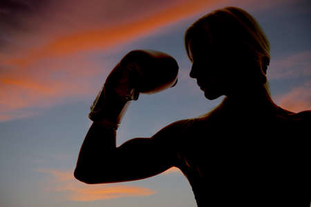 woman boxing gloves: A woman boxer is silhouetted in the colorful sky showing one arm.