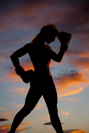 A woman is silhouetted in the colorful sky with boxing gloves. Фото со стока - 16008212