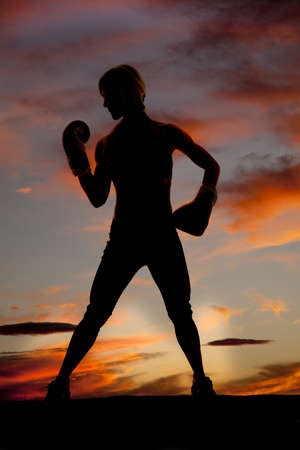A woman boxer is silhouetted in the colorful sky. photo