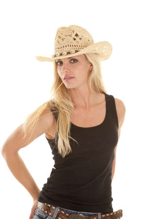 A woman with a piece of wheat in her mouth and a serious expression on her face.  She is wearing a cowboy hat and a black tank top. photo