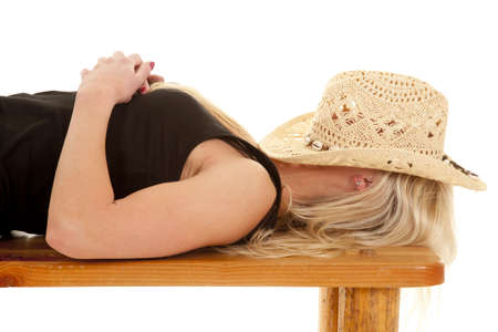 A woman is laying on a bench with a cowboy hat on her face. photo