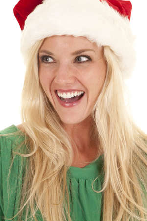 A woman in a green blouse and a santa hat is very excited. photo