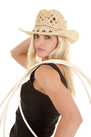 A woman is standing with a rope on her shoulder wearing a cowboy hat. photo