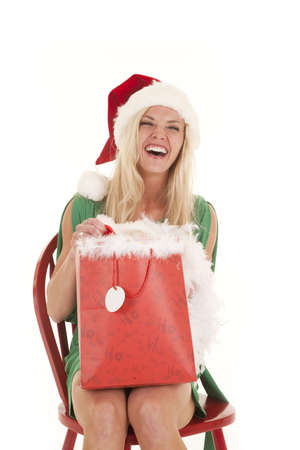 A woman in a santa hat laughing with a gift.