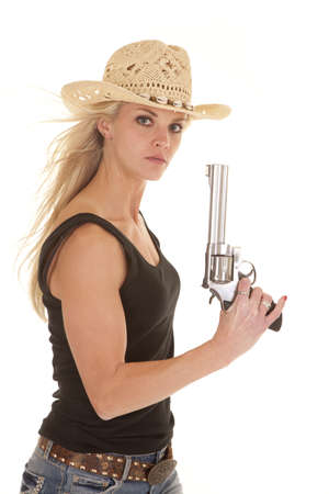 A woman looking at the camera holding a gun with a serious expression on her face wearing her cowgirl hat.