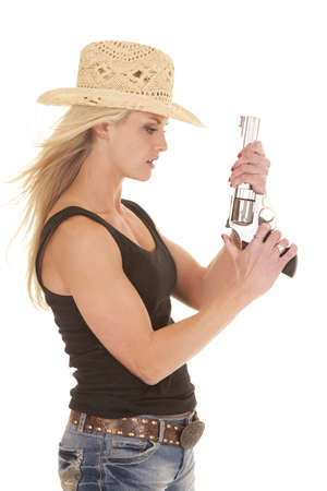 a cowgirl in her hat holding on to her weapon with a serious expression on her face.