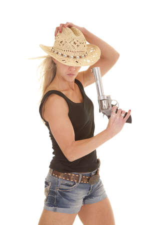 a woman looking down in her western wear holding on to a gun. photo
