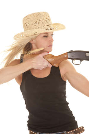 A woman aiming her shotgun with a serious expression. photo