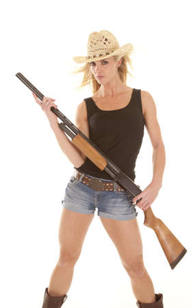 A cowgirl with a serious expression holding on to her rifle. photo
