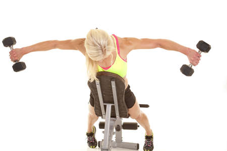 curls: a woman leaning on a bench doing a fly lift with weights. Stock Photo