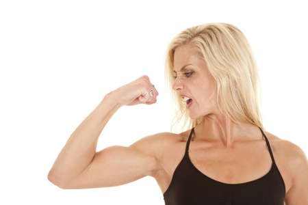 A woman looking at her arm while she is flexing with a upset expression on her face. photo