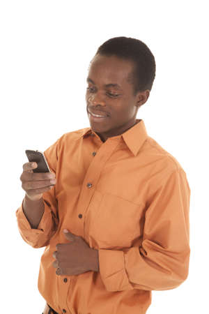 A man standing with his orange shirt on text-ing on his phone Stock Photo - 16035352