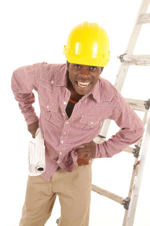 A man working construction with a hard hat on his head and plans in his hands with a smile on his face. photo