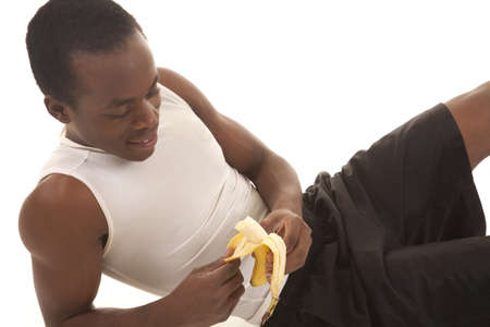 banana: a man laying down after a work out eating a banana