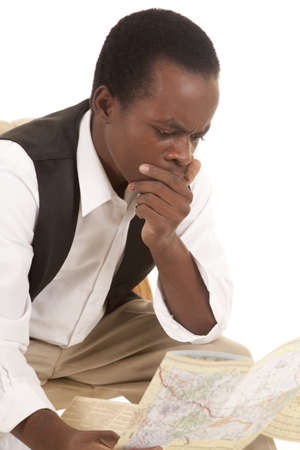 A man sitting and looking at a map with a shocked or confused expression on his face photo