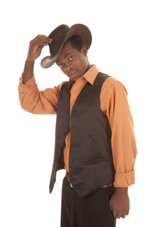 a man in his orange shirt and black vest putting on his cowboy hat. photo