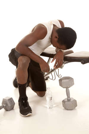 heavy weight: A man after a serious workout kneeling down on the floor looking tired. Stock Photo